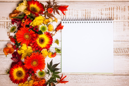 Blank notepad and autumnal flowers  on vintage wooden background. Top view with copy space Stock Photo