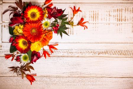 秋の草花とヴィンテージの木製の背景にベリー。コピー スペース平面図 写真素材