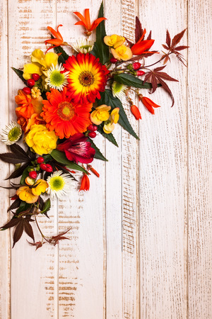 autumn arrangement: Autumnal flowers and berries on vintage wooden background. Top view with copy space