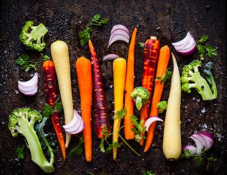 rainbow: raw rainbow carrot , broccoli and onion for roasting, on a baking tray