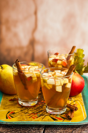 cocteles: El otoño y el invierno bebida con manzanas, peras y canela en vasos en la bandeja de la vendimia