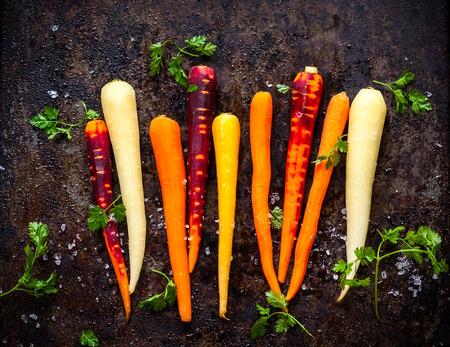 amarillo y negro: zanahoria arco iris prima para asar, en una bandeja para hornear Foto de archivo