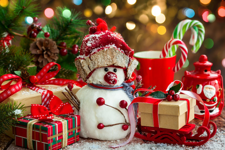Snowman, Christmas presents and sweets  over wooden background Stock Photo
