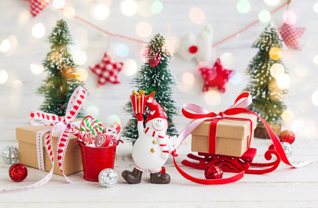 snowmangift boxes and decorative christmas trees on the white wooden background stock photo