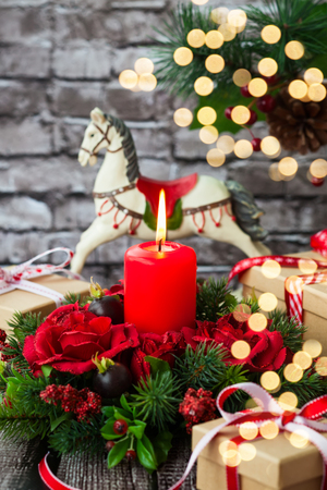 rocking horse: Christmas decorations with red candle,gift boxes and rocking horse on  the old wooden table Stock Photo