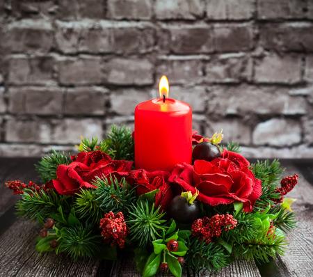 arreglo de flores: Decoración de mesa de Navidad con la quema de vela roja Foto de archivo