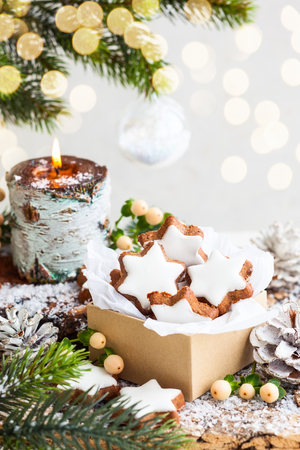 christmas candles: Christmas cookies in star shape and burning candle surrounded fir branches