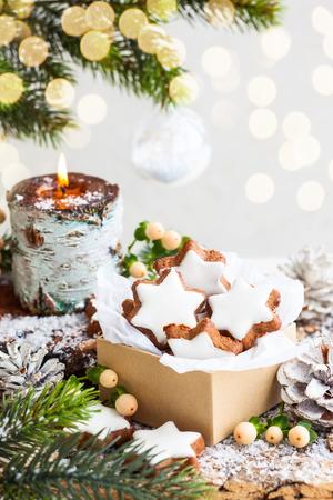 velas de navidad: Galletas de Navidad en forma de estrella y la vela encendida rodeados ramas de abeto Foto de archivo