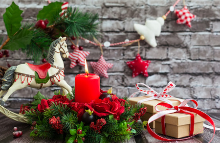 christmas candle: Christmas decorations with red candle,gift boxes and rocking horse on  the old wooden table Stock Photo