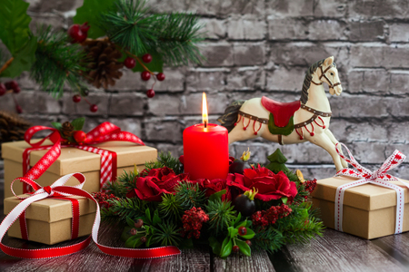 Christmas decorations with red candle,gift boxes and rocking horse on  the old wooden table Standard-Bild