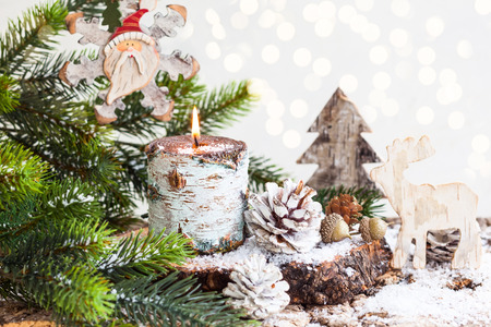 Christmas decorations with burning candle, wooden toys,fir branches and pine cones Banco de Imagens