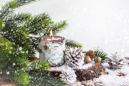 adviento: Decoración de Navidad con vela encendida, ramas de abeto y piñas