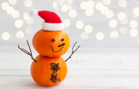 Happy snowman made out of tangerines,clove and winter berries Stock Photo