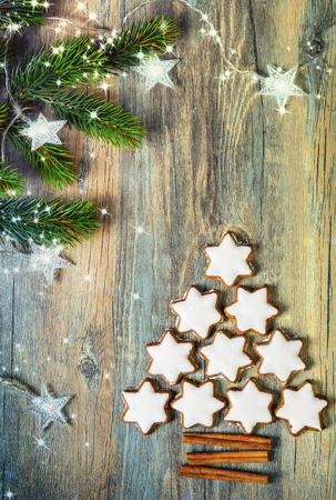 white christmas tree: Christmas background with gingerbread cookies,fir branches,christmas lights and spices on the old wooden board