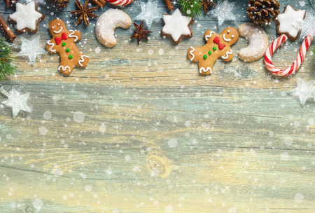 christmas lights background: Christmas decoration with gingerbread cookies,fir branches and spices on the old wooden board