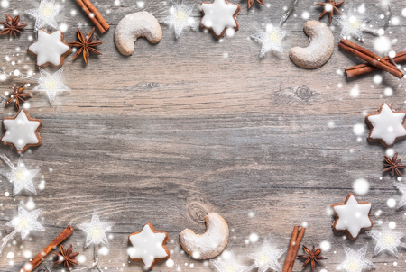 baking christmas cookies: Christmas background with gingerbread cookies,christmas lights and spices on the old wooden board. Image in cool vintage tone