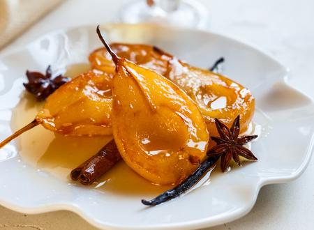 jarabe: Peras escalfados con especias en almíbar en la placa blanca. Postre delicioso para las vacaciones Foto de archivo