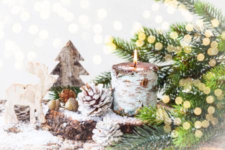 kerze: Weihnachtsschmuck mit brennenden Kerzen, Holzspielzeug, Tannenzweigen und Tannenzapfen