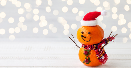 Happy snowman made out of tangerines,clove and winter berries Standard-Bild
