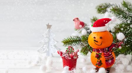 Gelukkige sneeuwman gemaakt van mandarijnen, kruidnagel en winter bessen Stockfoto