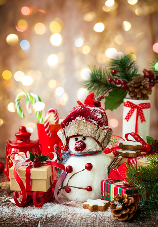 bonhomme de neige: Bonhomme de neige, des cadeaux de Noël et des bonbons sur fond de bois Banque d'images