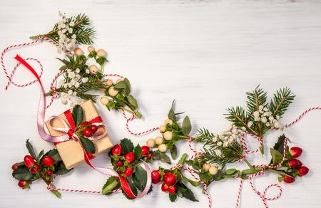 Kerstcadeautjes en winter natuurlijke slingers op de witte houten achtergrond