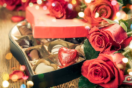 praline: Heart shaped box of chocolate truffles with red roses Stock Photo