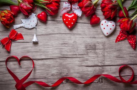 Valentinstag Hintergrund mit Pralinen, Herzen und roten Tulpen