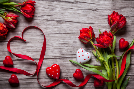 february: Valentines Day background with chocolates, hearts and red tulips