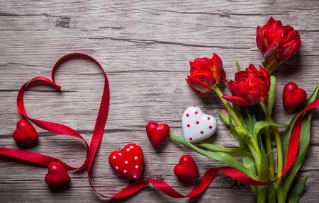 De achtergrond van de valentijnskaartendag met chocolade, harten en rode tulpen Stockfoto