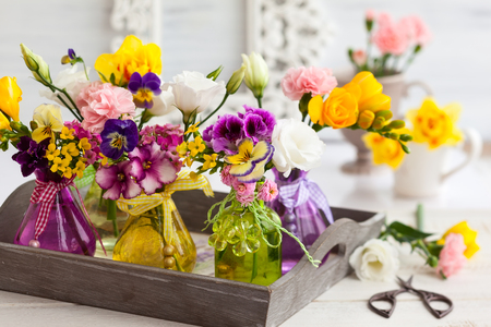 aroma: Beautiful fresh flowers in glass bottles on the wooden table