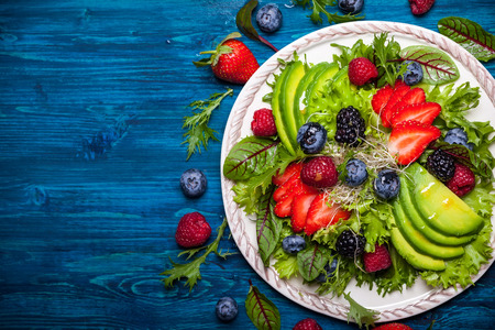 Mixed salad leaves with berries, avocado and honey-mustard dressing Stockfoto