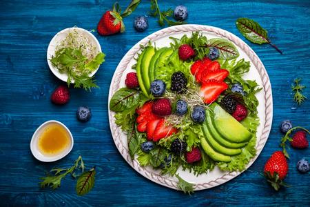 Gemengde slasoorten met bessen, avocado en honing-mosterd dressing Stockfoto