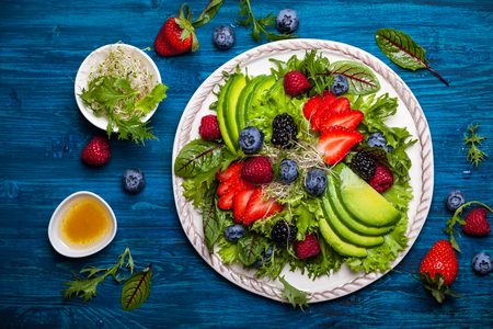 Mixed salad leaves with berries, avocado and honey-mustard dressing Imagens
