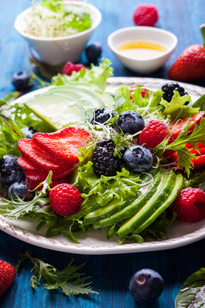 Mixed salad leaves with berries, avocado and honey-mustard dressing 스톡 콘텐츠