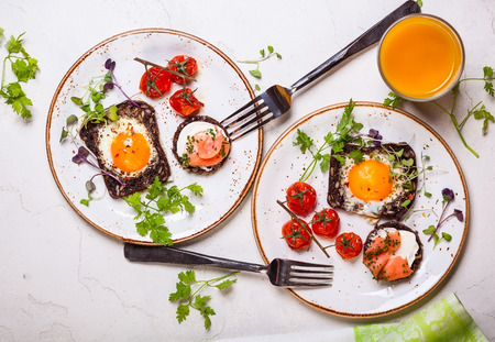 pain: Oeufs frits sur des tranches de pain de grains entiers, canape de saumon et tomates cerises cuites