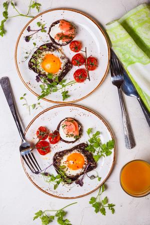 huevos fritos: Huevos fritos en rodajas de pan de grano entero, canapé de salmón y tomates cherry al horno