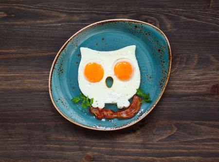 huevos fritos: huevos fritos con forma de búho con tocino crujiente en una placa