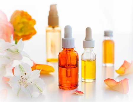 essence: Bottles of essential aromatic oils and fresh flowers Stock Photo