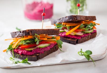 bocadillo: gluten bocadillos veganos libres con hummus de remolacha, vegetales crudos y brotes Foto de archivo
