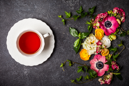 Cup of tea and various flowers on black background. Overhead view with copy space