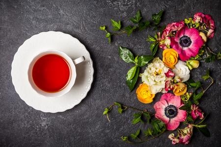 taza de té: Taza de té y diversas flores sobre fondo negro. Vista de arriba, con copia espacio