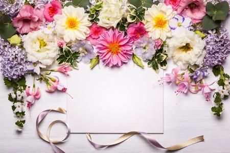 Festliche Blumenkomposition mit Grußkarte auf dem weißen hölzernen Hintergrund. Draufsicht