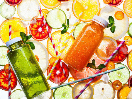 assorted: Bottles of fresh juice on the citrus background. Transparent pattern. Stock Photo