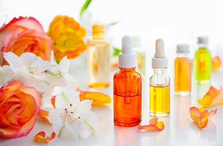 Bottles of essential aromatic oils and fresh flowers Stock Photo