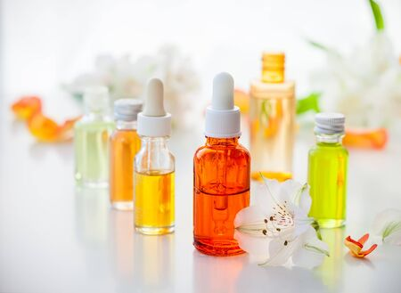 bath essence: Bottles of essential aromatic oils and fresh flowers Stock Photo