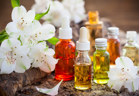 cosmetic product: Bottles of essential aromatic oils and fresh flowers Stock Photo