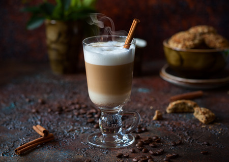 tall glass: Coffee latte in a tall glass with stick of cinnamon