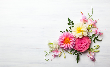 Festive flower composition on the white wooden background. Overhead view Фото со стока