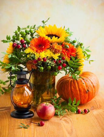 Autumn still life with flowers, pumpkin and fruits Standard-Bild